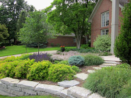 The upper terraced planting includes a secondary stone path down to the lower lawn.