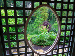 An oval window provides a sneak preview of this expansive woodland garden.