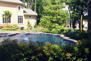 A swimming pool and spa in trefoil shape nested into a wood-side garden.