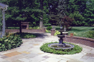 Bluestone rear patio with brick seat wells, fireplace & iron fountain.