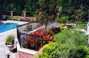 Brick walls and iron fencing add structure to multi-level pool garden.