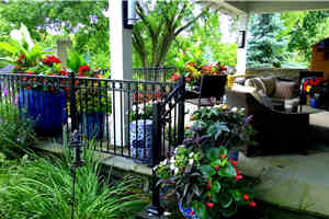 Wrought iron fencing, a rooftop bluestone entertainment area,  and a beautiful fireplace are complemented with harmonious ceramic urns filled with large tropicals and long blooming annuals especially for hummingbirds, pollinating bees and butterflies, as well as strategic privacy.